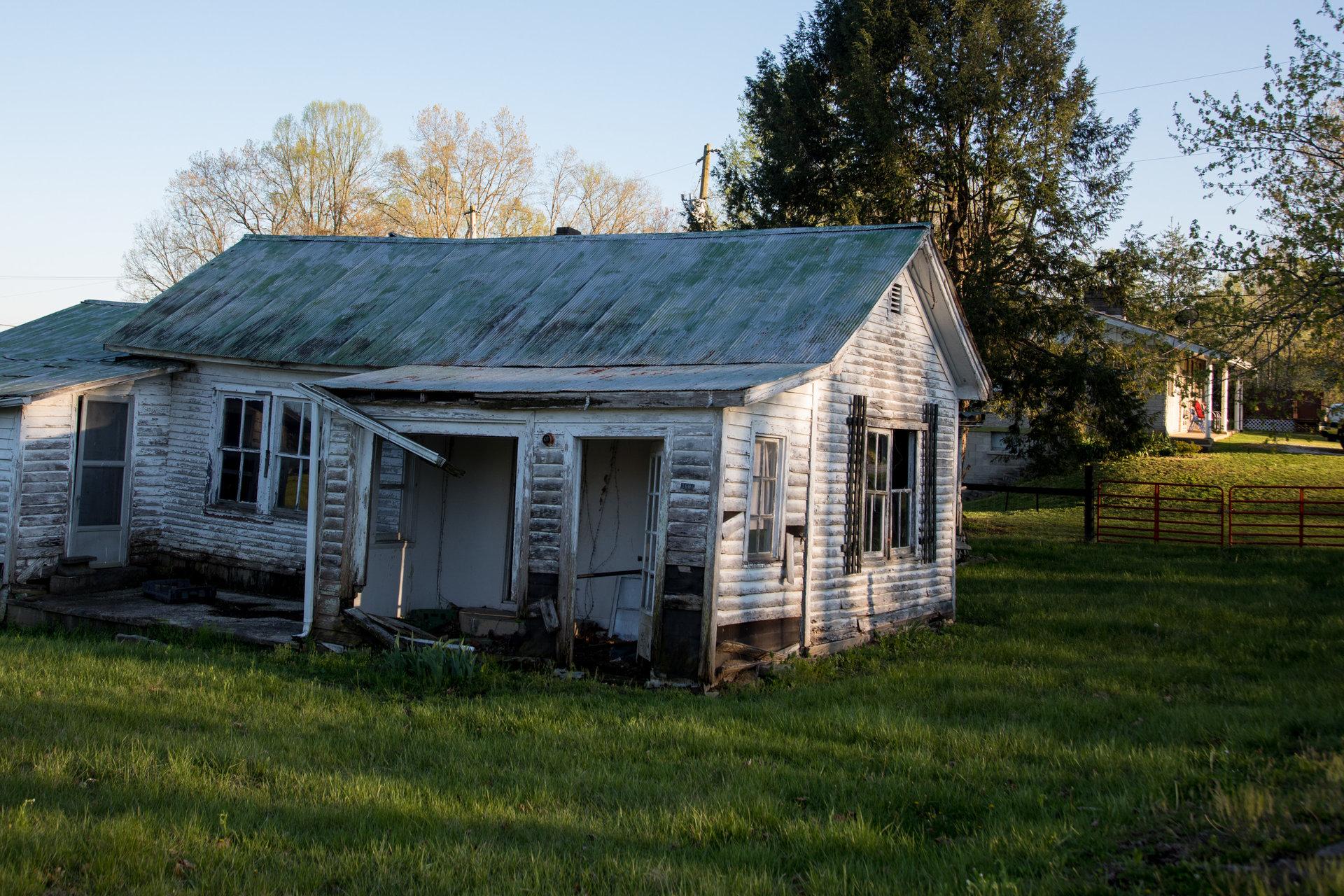 Une maison abandonnée, devant une nouvelle construction.